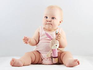 Hintergrundbilder Spielzeuge Grauer Hintergrund Baby Sitzt Starren Kinder