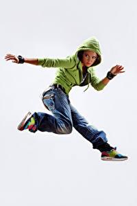 Fotos Weißer hintergrund Sprung Jacke Jeans Hand Bein Mädchens
