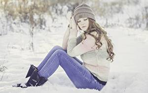 Bilder Winter Schnee Braune Haare Sitzen Mütze Bein Jeans Sweatshirt Mädchens