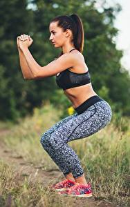Fotos Fitness Gras Braunhaarige Seitlich Posiert Bokeh Hand junge frau Sport