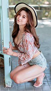 Bilder Asiaten Posiert Sitzen Shorts Bluse Der Hut Lächeln Starren Mädchens