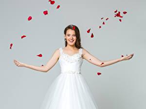 Fotos Grauer Hintergrund Braune Haare Braut Lächeln Kleid Blütenblätter Mädchens