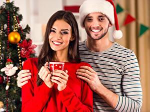 Fotos Neujahr Mann Zwei Mütze Lächeln Braunhaarige Hand Mädchens