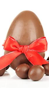 Fotos Süßware Schokolade Ostern Weißer hintergrund Eier Schleife Lebensmittel