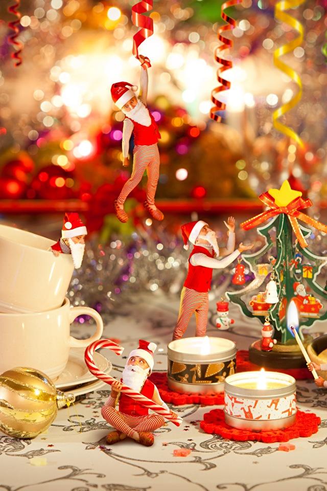 Fotos Neujahr Mütze Weihnachtsmann Flamme Tasse sitzt Kerzen Feiertage 640x960 Feuer sitzen Sitzend