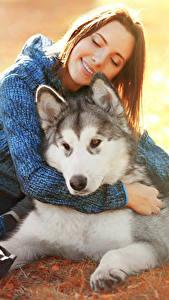 Hintergrundbilder Hunde Siberian Husky Braunhaarige Lächeln Sitzend Mädchens Tiere
