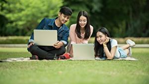 Bilder Mann Weibliche studenten Sitzen Gras Drei 3 Brünette Notebook Mädchens