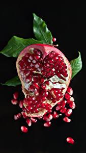 Fotos Granatapfel Schwarzer Hintergrund Getreide Lebensmittel