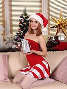 Fotos Neujahr Weihnachtsbaum Couch Geschenke Mütze Rotschopf Blick Lächeln junge Frauen