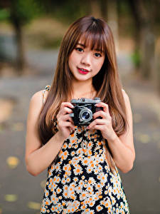 Bilder Asiaten Braune Haare Bokeh Fotoapparat Hand Blick Mädchens