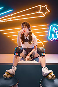 Bilder Asiatische Sitzen Bein Rollschuh Starren Mädchens