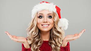 Fotos Neujahr Grauer Hintergrund Blond Mädchen Lächeln Mütze Hand Mädchens