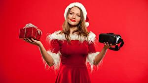 Fotos Neujahr Roter Hintergrund Braune Haare Kleid Geschenke Lächeln Hand Mädchens