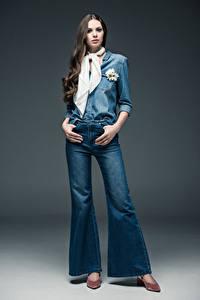 Fotos Grauer Hintergrund Braunhaarige Jeans Haar Mädchens