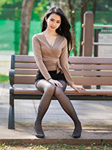Fotos Asiatische Brünette Bank (Möbel) Sitzend Bein Rock Bluse Blick junge Frauen