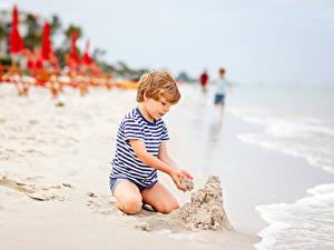 Bilder Strände Sand Junge Sitzend kind