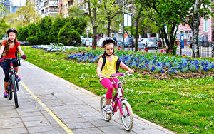 Desktop hintergrundbilder Kleine Mädchen Zwei Fahrräder Bewegung Helm Kinder