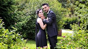 Fotos Paare in der Liebe Mann Zwei Brünette Lächeln Anzug Kleid