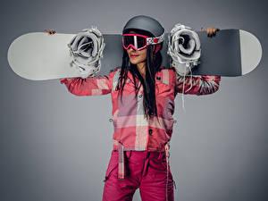 Hintergrundbilder Snowboard Grauer Hintergrund Braunhaarige Helm Brille Mädchens Sport