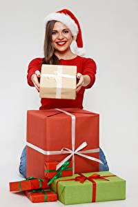 Hintergrundbilder Neujahr Grauer Hintergrund Braune Haare Lächeln Blick Mütze Geschenke Mädchens