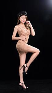 Fotos Asiatisches Schwarzer Hintergrund Pose Kleid Bein Braune Haare Blick Model Mädchens
