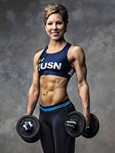 Fotos Fitness Bodybuilding Grauer Hintergrund Starren Lächeln Hand Hanteln Bauch junge Frauen