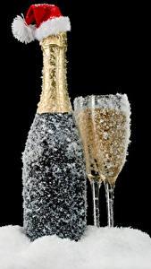 Fotos Neujahr Schaumwein Schwarzer Hintergrund Flasche Weinglas Schnee Mütze Lebensmittel