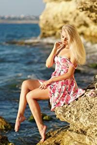 Bakgrunnsbilder Havet Blond jente Kjole Klippe Hatt Sitter Ben ung kvinne