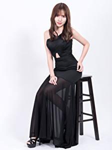 Bilder Asiaten Weißer hintergrund Stühle Sitzt Kleid Schwarz Braune Haare junge frau