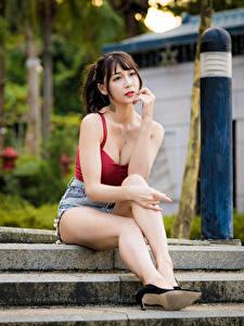 Fotos Asiatisches Unscharfer Hintergrund Sitzend Bein Shorts Unterhemd Blick Mädchens