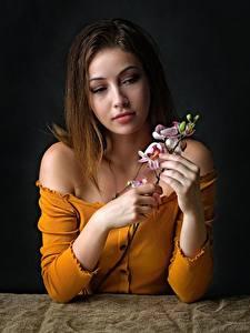 Fotos Orchidee Sitzt Hand Ast Braune Haare junge frau