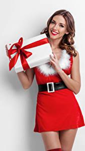 Bilder Neujahr Weißer hintergrund Braunhaarige Lächeln Kleid Geschenke junge Frauen