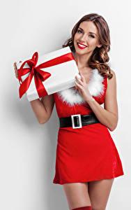 Bilder Neujahr Weißer hintergrund Braunhaarige Lächeln Kleid Geschenke