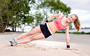 Fotos Fitness Strände Sand Körperliche Aktivität Lächeln Bein Shorts Mädchens Sport