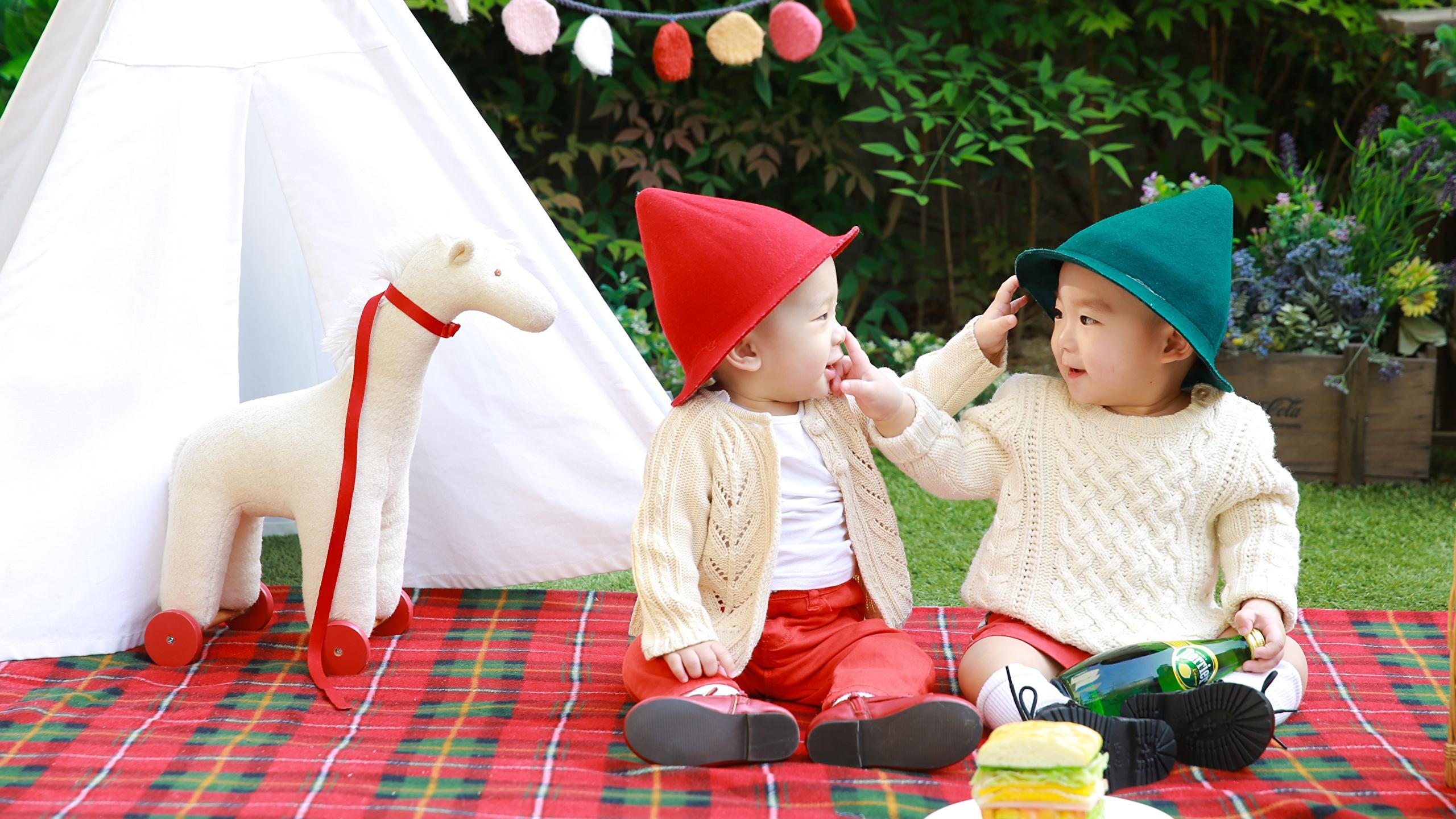 Bilder von jungen Kinder 2 Mütze Sweatshirt Asiatische sitzt 2560x1440 Junge Zwei sitzen Sitzend