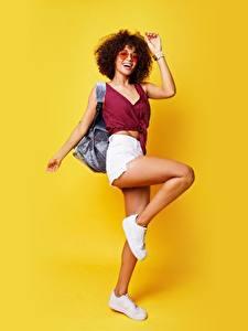 Hintergrundbilder Posiert Shorts Bein Unterhemd Brille Farbigen hintergrund Mädchens