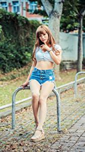 Fotos Asiatische Sitzt Bein Shorts Hand junge frau
