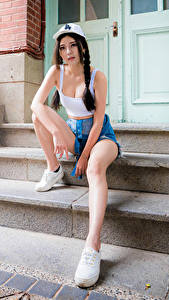Fotos Asiatische Stiege Sitzt Bein Shorts Unterhemd Baseballkappe Starren Zopf junge frau
