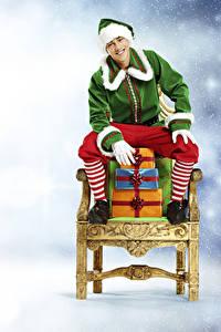 Fotos Neujahr Elfen Sessel Geschenke Sitzend Uniform Lächeln