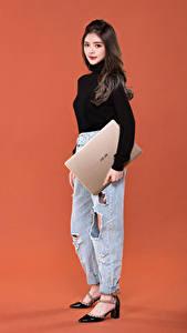 Hintergrundbilder Farbigen hintergrund High Heels Jeans Notebook Braune Haare Starren  junge frau Computers