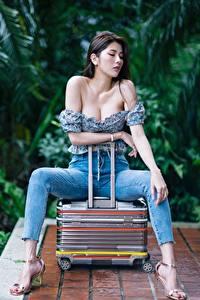 Fotos Asiatische Koffer Jeans Hand Bein Stöckelschuh Sitzend Dekolleté Brünette Bokeh Posiert junge frau