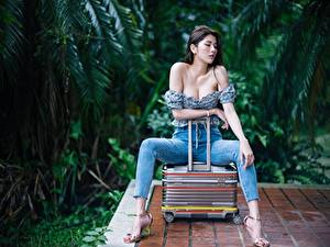 Photo Asian Suitcase Jeans Hands Legs Stilettos Sitting Neckline Brunette girl Bokeh Posing young woman