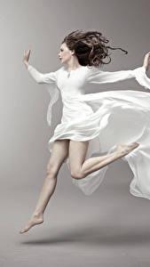 Fotos Grauer Hintergrund Braunhaarige Kleid Laufsport Mädchens