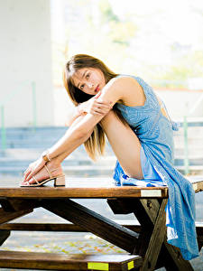 Fotos Asiaten Tisch Sitzen Bein Kleid Braunhaarige Blick junge frau