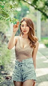Fotos Asiaten Unscharfer Hintergrund Posiert Hand Shorts Unterhemd Braune Haare junge frau