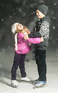 Images Two Boys Little girls Ice skate Winter hat Smile Snow child Sport