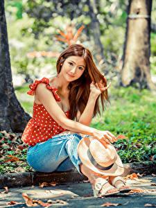 Fotos Asiaten Sitzt Jeans Der Hut Braune Haare Starren Bluse junge frau