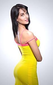 Bilder Model Grauer Hintergrund Brünette Pose Starren Kleid Nora Fatehi