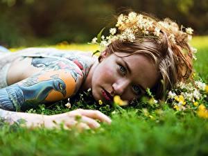 Bilder Unscharfer Hintergrund Gras Gesicht Blick Tätowierung Hand Piercing Liegen junge frau