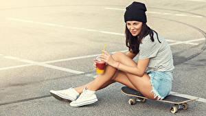 Bilder Skateboard Asphalt Braunhaarige Mütze Trinkglas Sitzt junge frau Sport